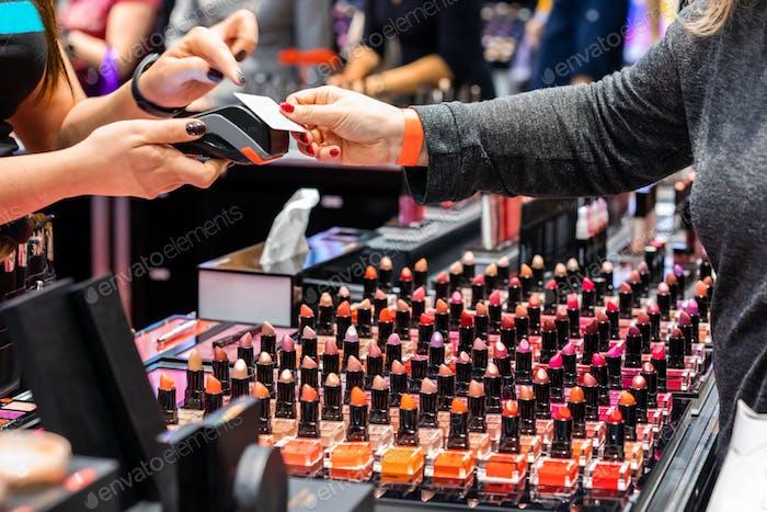 Kunden Frau zahlen für ein Produkt mit Kreditkarte im Beauty-Shop