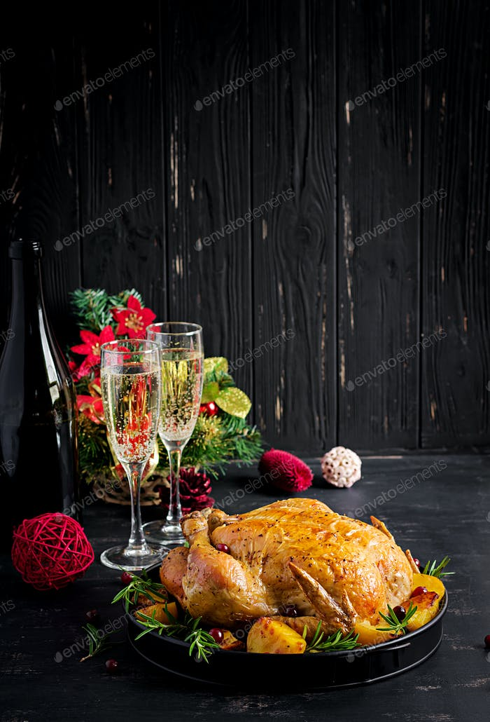 he Christmas table is served with a turkey, decorated with bright tinsel.