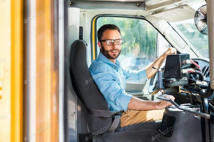 водитель школьного автобуса сидит внутри автобуса и тянет рычаг