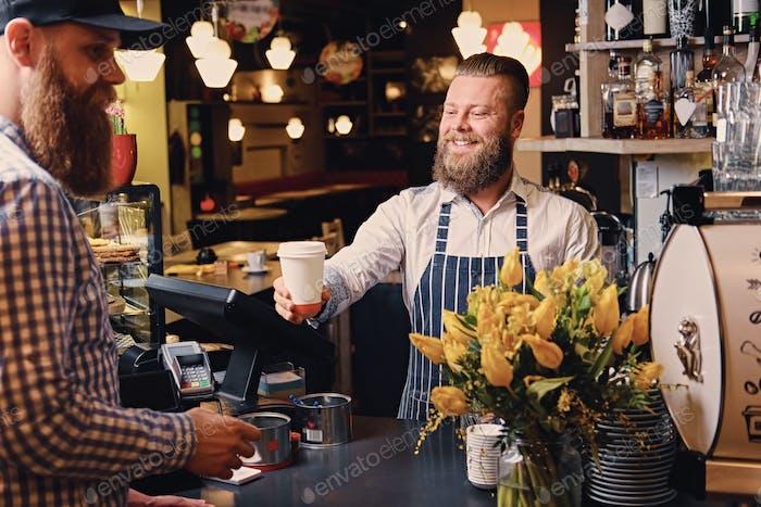 Человек, продающий кофе потребителю в кофейне.