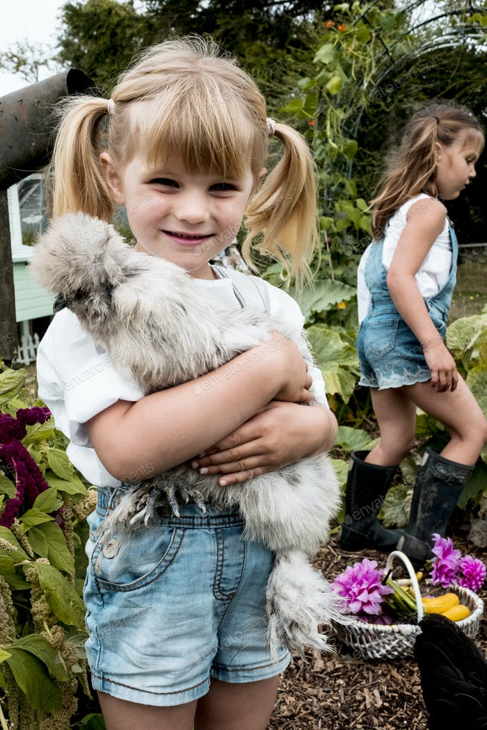 Blond girl standing in a garden, holding fluffy grey chicken.