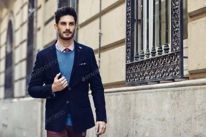 Attractive man wearing british elegant suit in the street. Modern hairstyle
