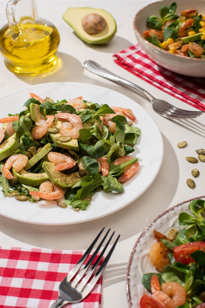 Selective Focus of Fresh Green Salad With Shrimps And Avocado on Plates Near Forks And Oil