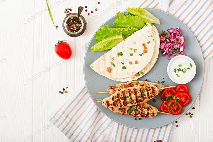 Minced Lula kebab grilled turkey (chicken) with fresh vegetables. Top view