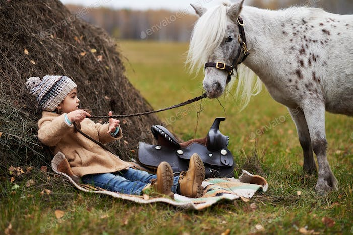 Girl Spending Time With Pony On Hayfield