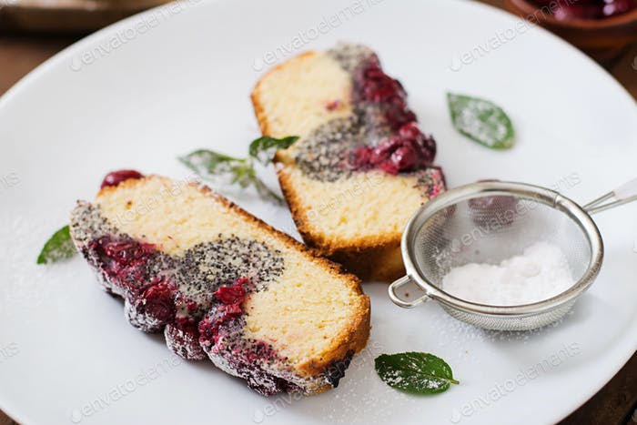 Thumbnail for Cherry poppy seed cake dusted with powdered sugar on a wooden table