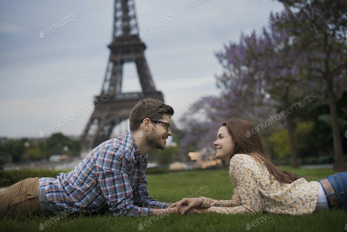 A couple lying on the grass holding hands under the shadow of the Eiffel Tower in Paris.