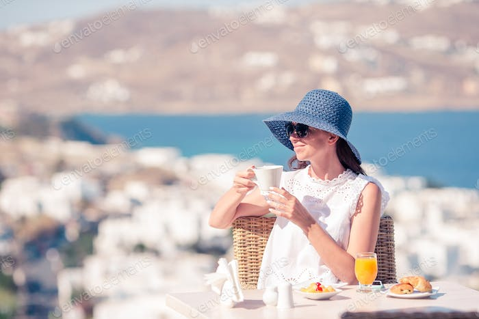 Young woman with coffee at outdoor cafe with amazing view on Mykonos town