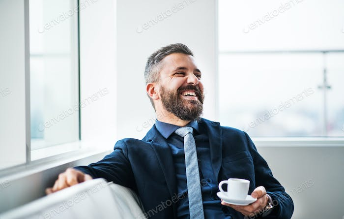 A portrait of businessman with a cup of coffee sitting on a sofa.