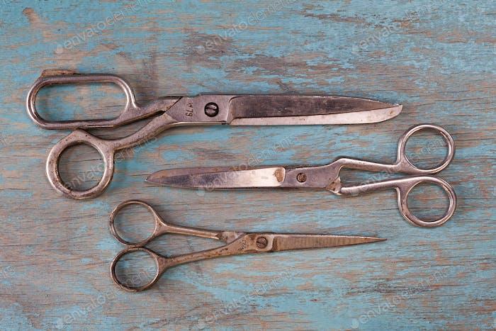 A set of vintage scissors on blue wooden background