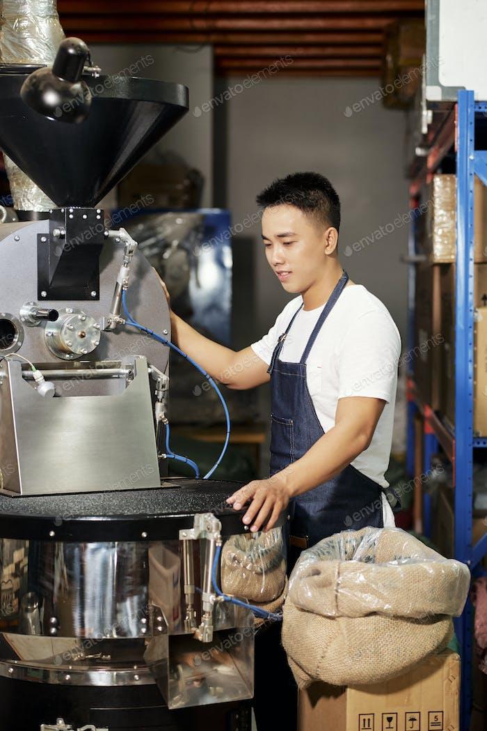 Young man roasting coffee