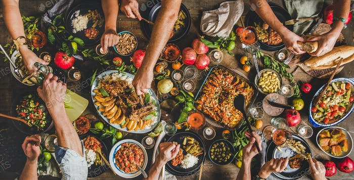 Flat-lay of peoples hands and Turkish foods over rustic table