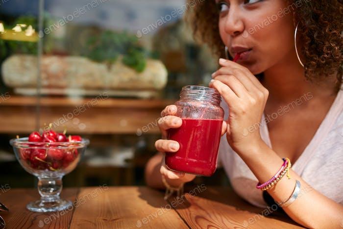 Young woman having fresh fruit juice