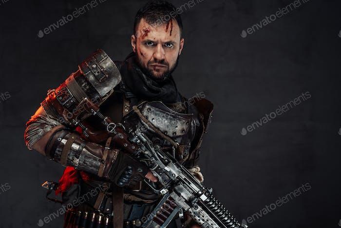 Serious stalker with damaged head and shotgun in dark background