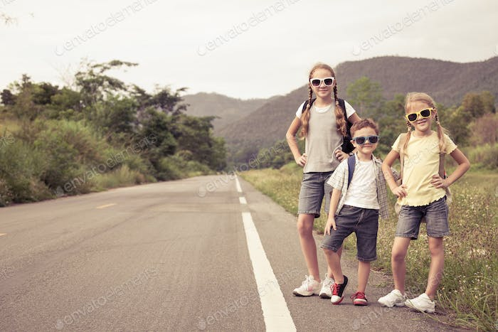 Happy children  walking on the road at the day time.