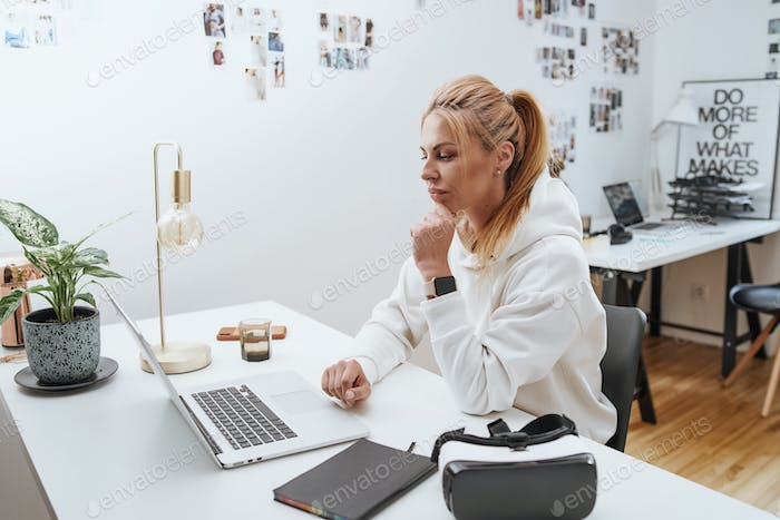 Beautiful female businessperson types on laptop sitting at table