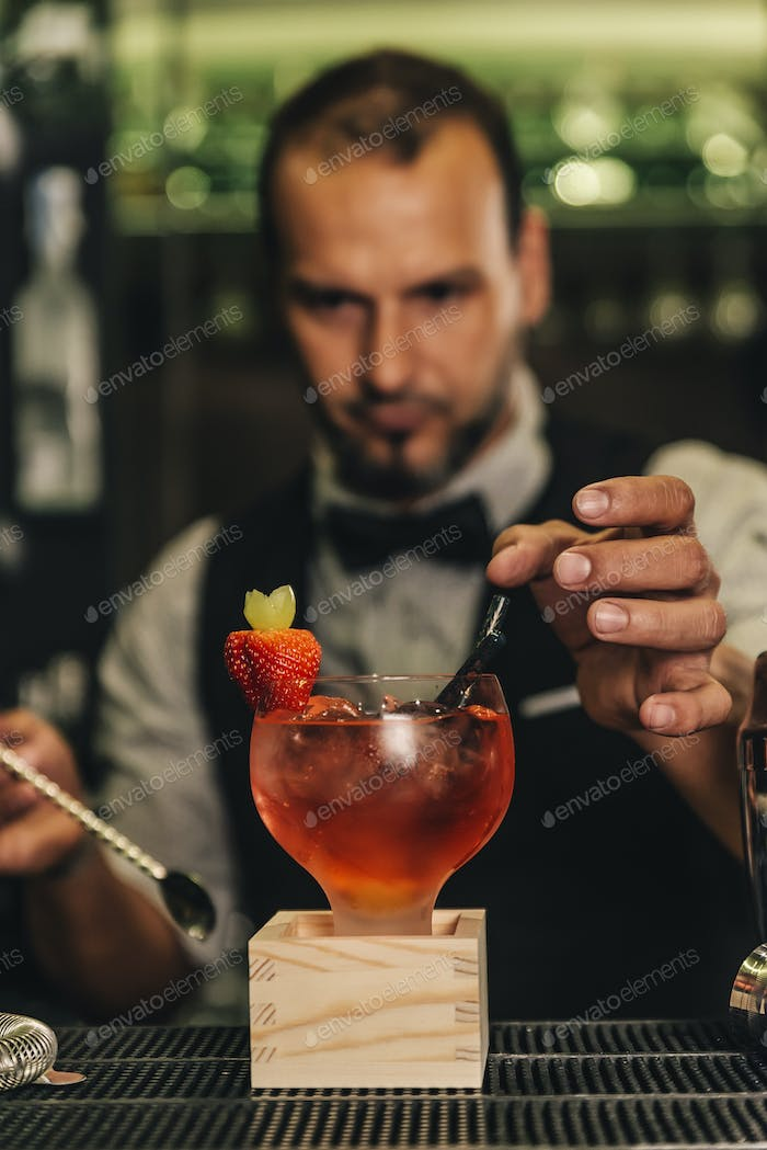 Barman is making cocktail at night club