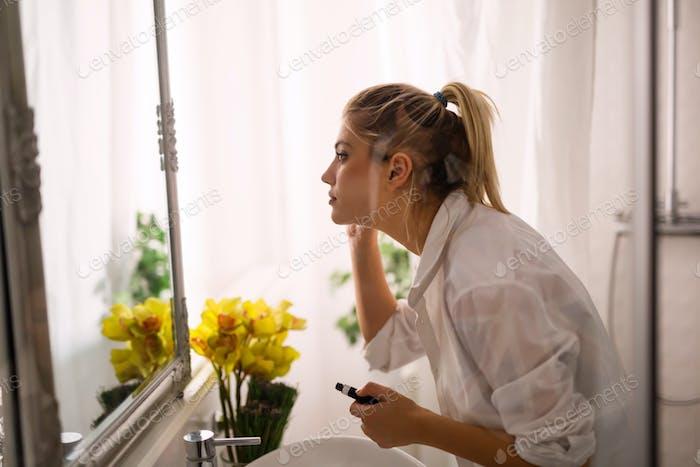 Beautiful woman applying makeup