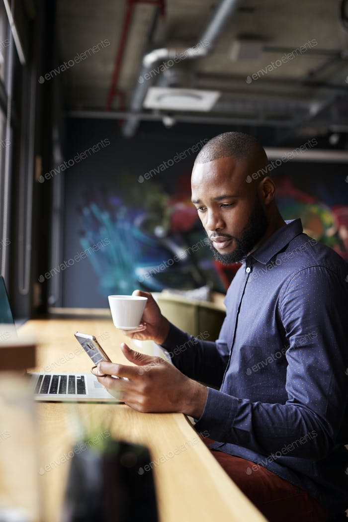 Mid adult black male creative sitting by window having coffee using smartphone, side view, vertical
