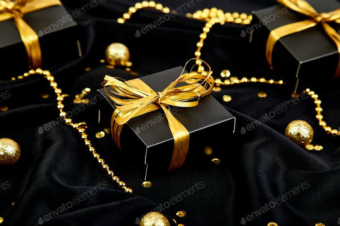 luxury black gift boxes with gold ribbon photo by bondarillia on