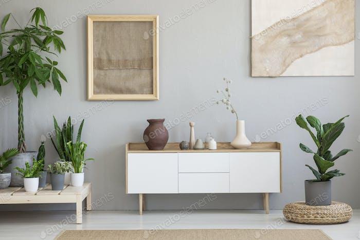 Poster auf grauer Wand über weißem Schrank im Wohnzimmer interio