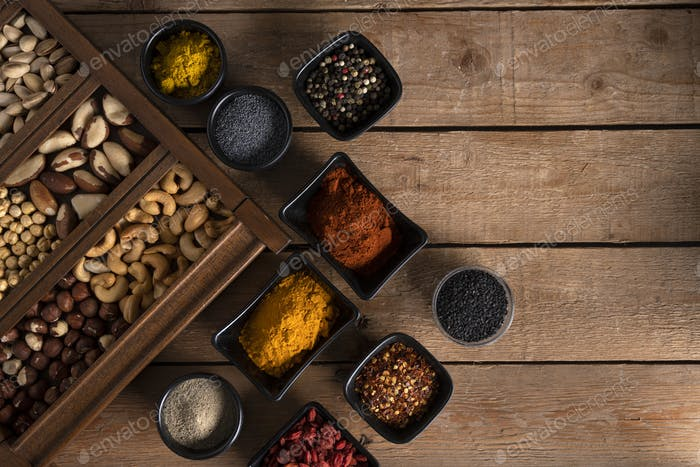 Nuts in a wooden box and spices in different shape of bowls