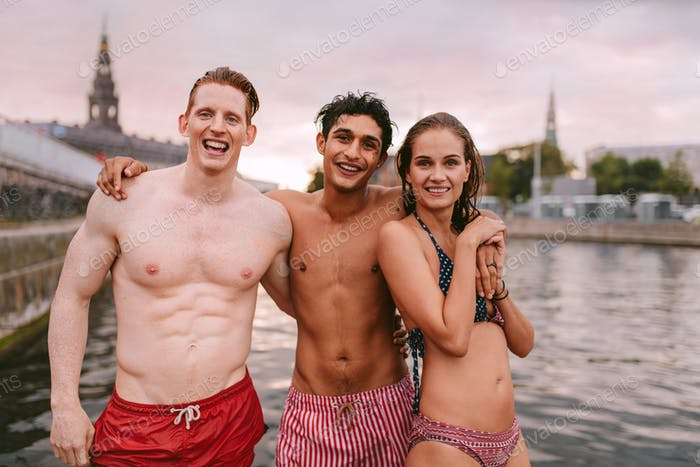 Young people in swimwear standing by a lake