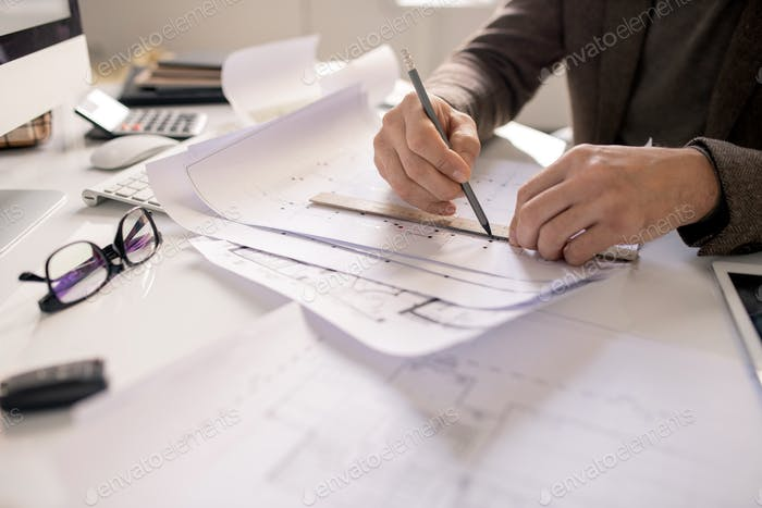 Hands of architect with pencil and ruler drawing line while working over sketch