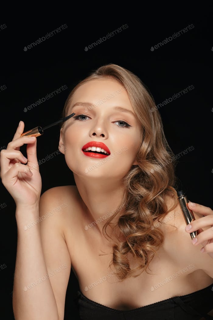 Portrait of young attractive woman with wavy hair and red lips a