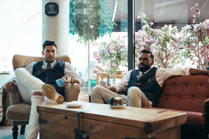 Zwei gut aussehende Männer mit Kaffee