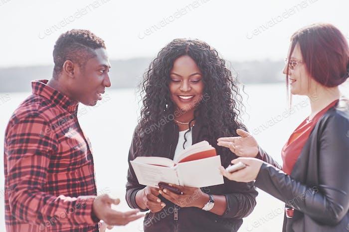 Eine Gruppe junger multinationaler Menschen mit einem Buch, Studenten, die im Freien studieren