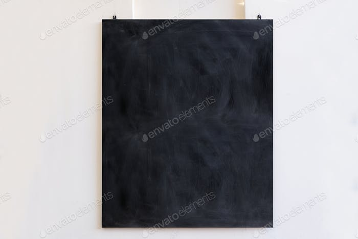 Blackboard hanging on white wall background. Black blank board, school education sign, mockup,