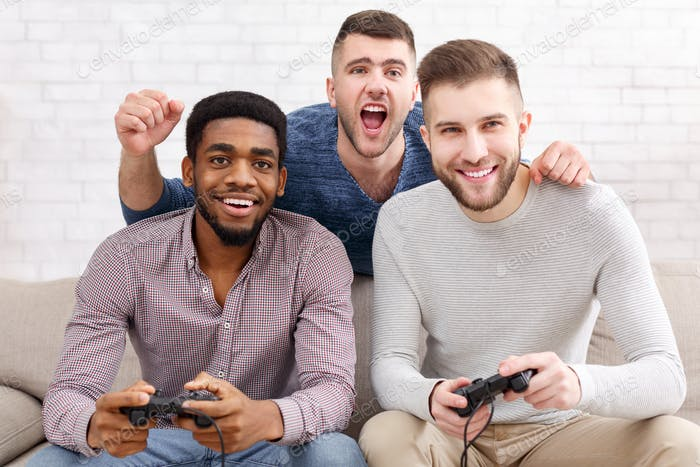 Gamers. Excited men playing video game at home