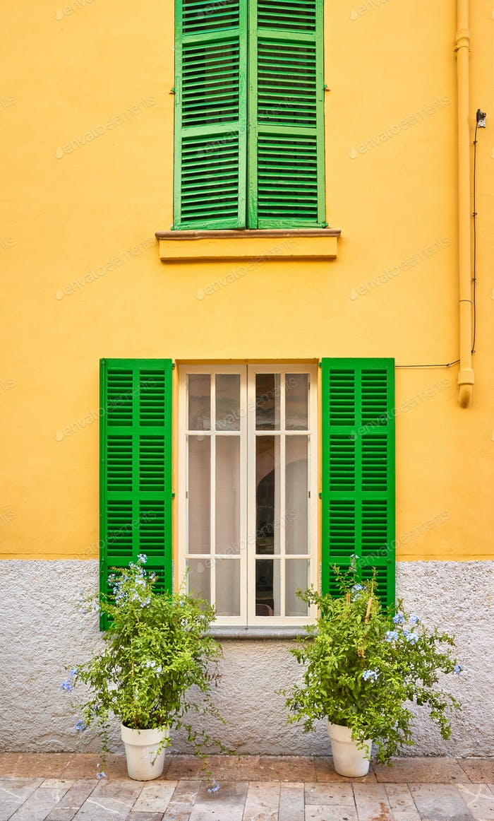 Green shutters on yellow wall.