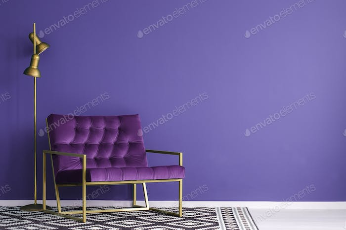 Ultra violet armchair with golden details and lamp standing on t
