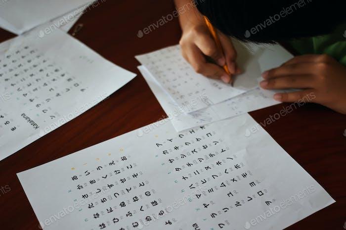 Un niño trata de escribir caracteres japoneses