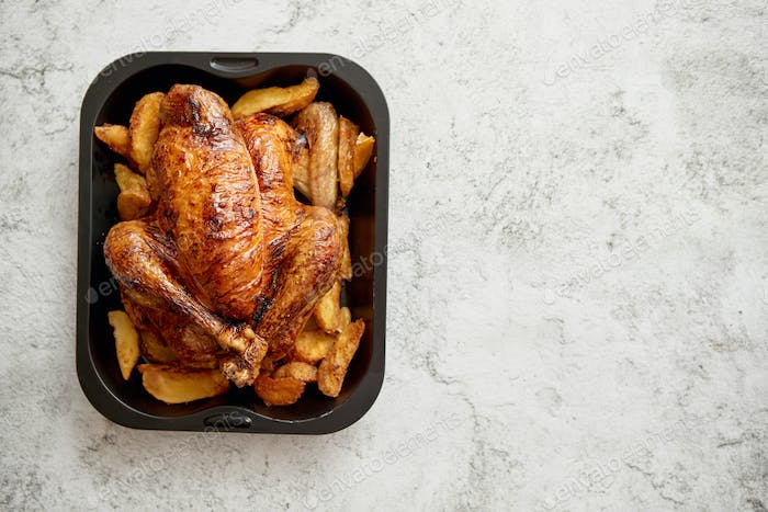 Roasted chicken or turkey with potatoes in black steel mold
