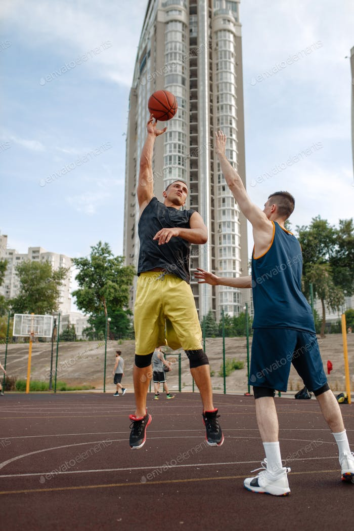 Two basketball players playing on outdoor court