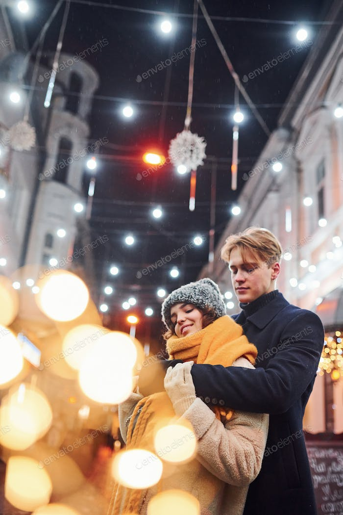 Happy young couple in warm clothes is on christmas decorated street together