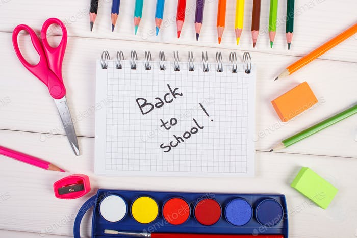 School accessories on white boards, back to school inscription in notepad