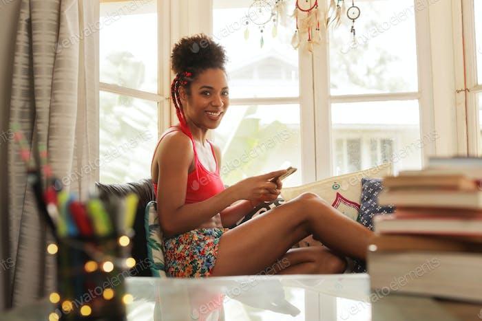 jóvenes Mujer mensajes de texto en teléfono y mirando en cámara
