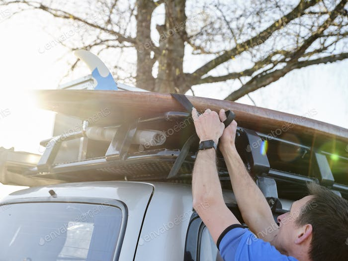 Man fastening paddleboard to roof of car