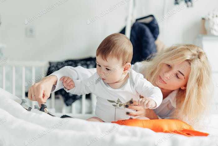 mother playing with her baby in the bedroom