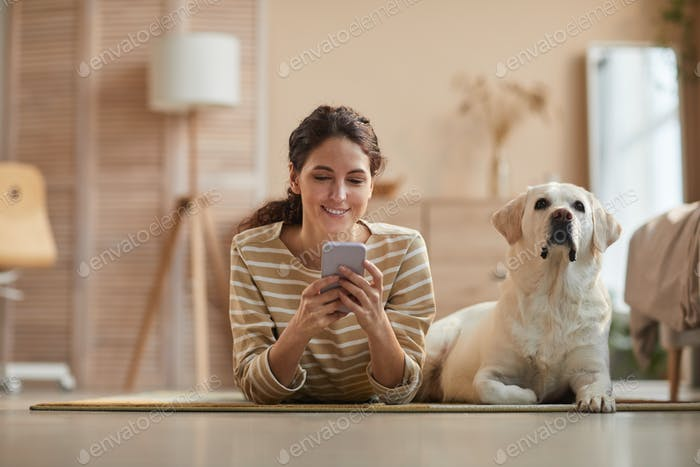 Happy Woman using Smartphone with Dog at Home
