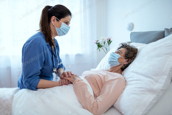 Home Caregiver Comforting Senior Female Patient Lying in Bed.