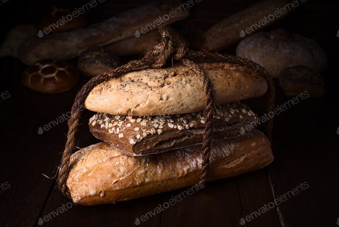 rustic homemade breads tied with ropes on dark wooden stage