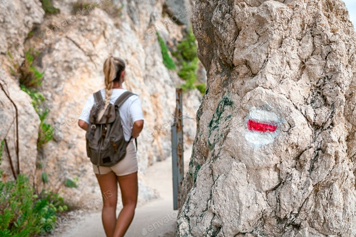 Hiking trail sign on rock and tourist woman walking on path