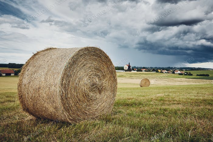 Straw bales stacked on field against storm