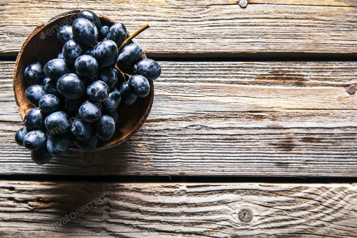 Top view of grapes in basket on wooden table. fruits