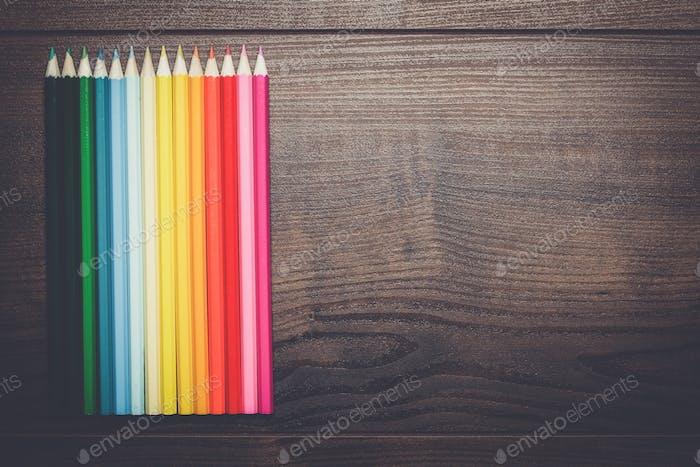 Bunte Bleistifte über braunen Holztisch Hintergrund